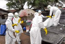 Health workers carry load the  body of a woman that they suspect died from the Ebola virus, onto a truck in front of a makeshift shop in an area known as Clara Town in Monrovia, Liberia, Wednesday, Sept. 10, 2014. A surge in Ebola infections in Liberia is driving a spiraling outbreak in West Africa that is increasingly putting health workers at risk as they struggle to treat an overwhelming number of patients. A higher proportion of health workers has been infected in this outbreak than in any previous one. (AP Photo/Abbas Dulleh)